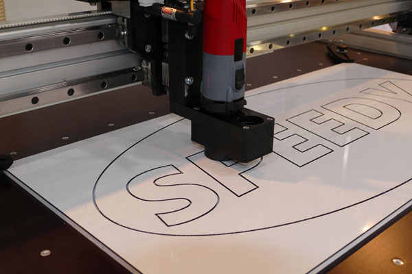 CNC router work cutting out design from plastic